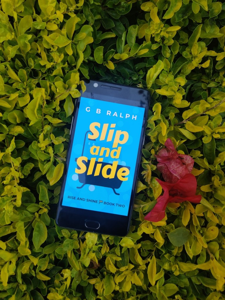 Slip and Slide cover displayed on phone in front of hedge. Photo credit: Sneha Jaiswal (ABSTRACT AF)