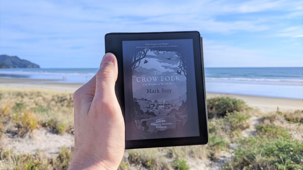 The Crow Folk (The Witches of Woodville 1) by Mark Stay. Photo of book cover on Kindle at the beach.