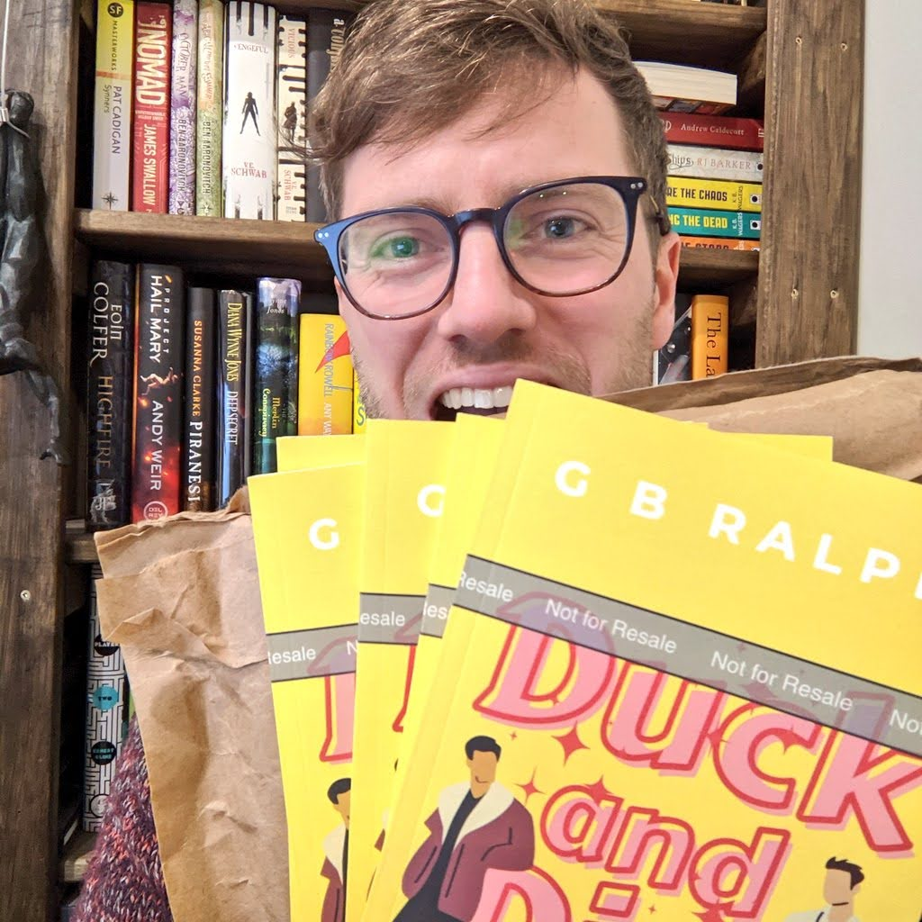 Author holding up Duck and Dive paperback book proof copies